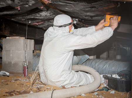 Worker stapling insulation under floor of manufactured home