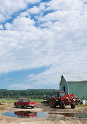 Barn and tractor under partly cloudy sky