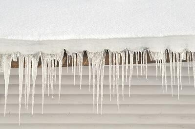 Snow and icicles cling to roof