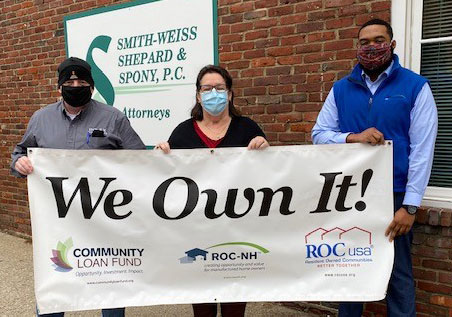 Two Jewel Estates board members and a ROC-NH hold the We Own It banner presented to Jewel Estates.