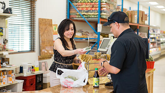 A cashier at Saigon Asian Market in Manchester, a CDFI-supported business.
