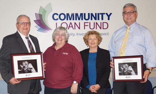 Two men and two women pose in front of Community Loan Fund logo