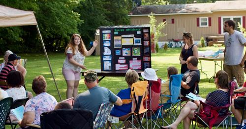 Mascoma Meadows residents sit in folding chairs outdoors and learn about the solar project.