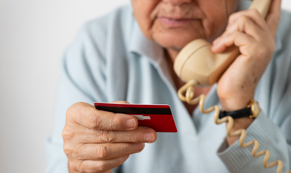 A senior reads their credit card number into a phone.