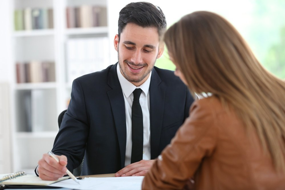 Young man in suit and tie using pen and paper to explain to young woman.