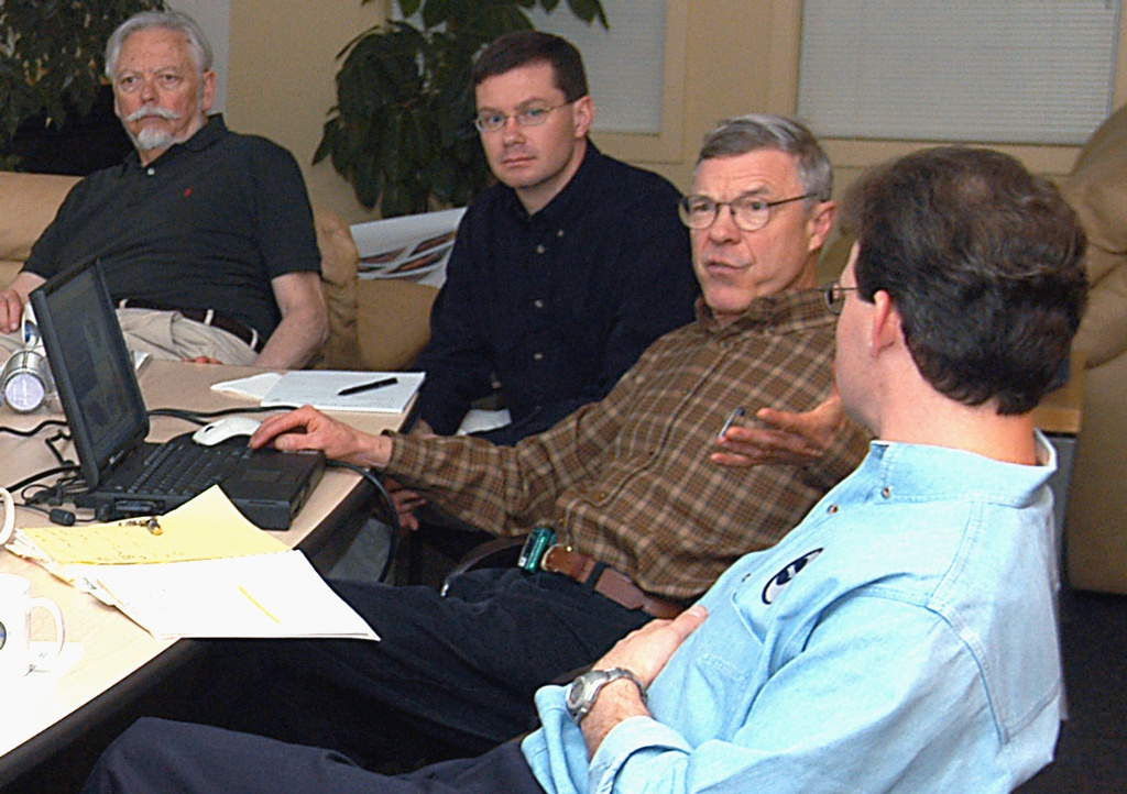 Four men have a discussion around a table.