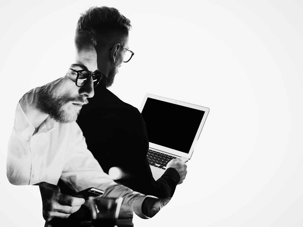 Double-exposure image of young businessman looking at laptop.