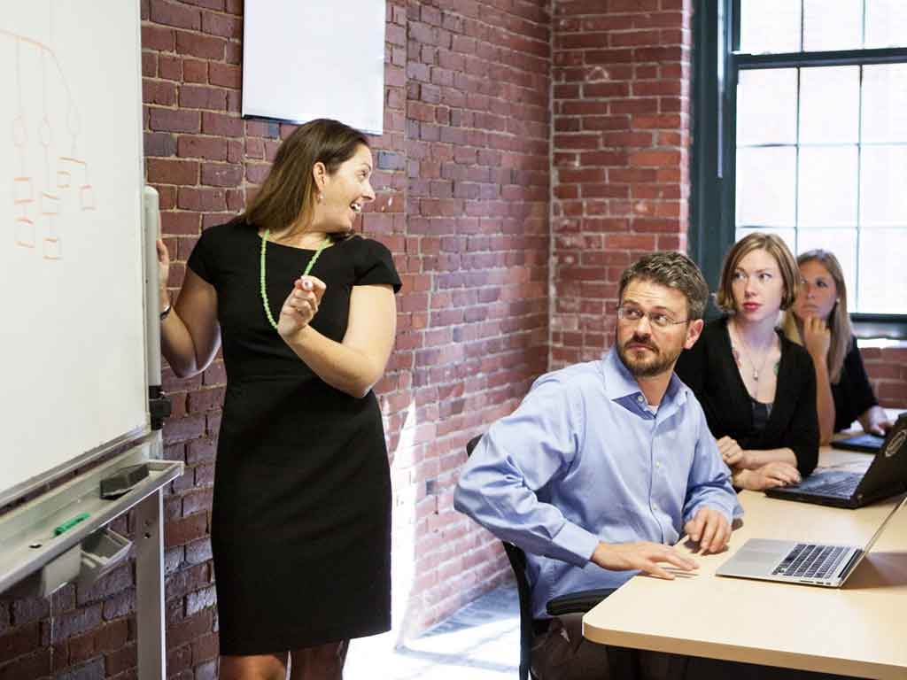 Woman illustrates a concept on a whiteboard for three employees.